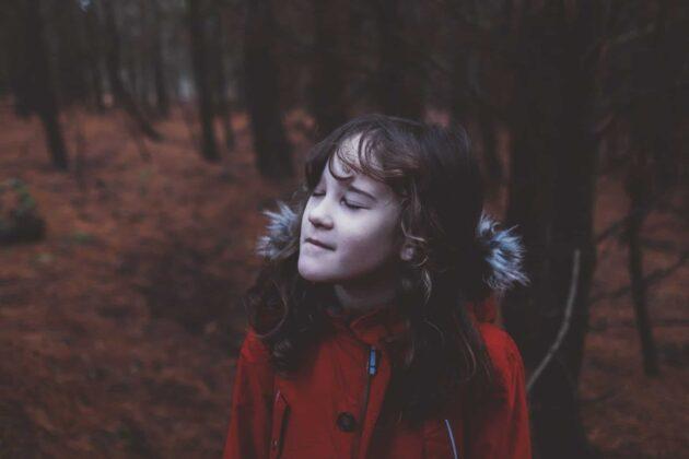 child closing eyes outside